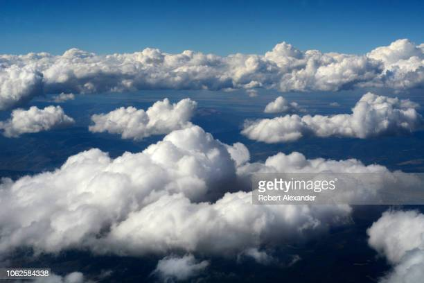 Cumulus clouds float above California as seen from a window in a passenger plane approaching San Francisco.
