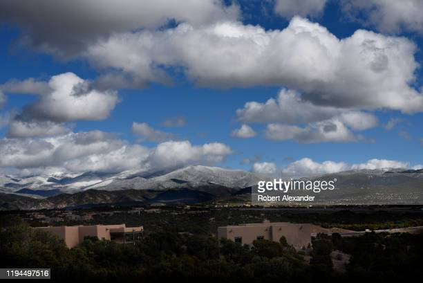 Cumulus clouds form over the snowcovered Sangre de Christo Mountain near Santa Fe New Mexico