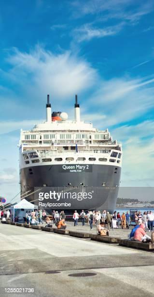 cunards flaggschiff, the queen mary 2, ragt über der hübschen norwegischen hafenstadt stavanger, während sie angedockt wird, während die passagiere abfahren und die stadt erkunden. - passagier wasserfahrzeug stock-fotos und bilder