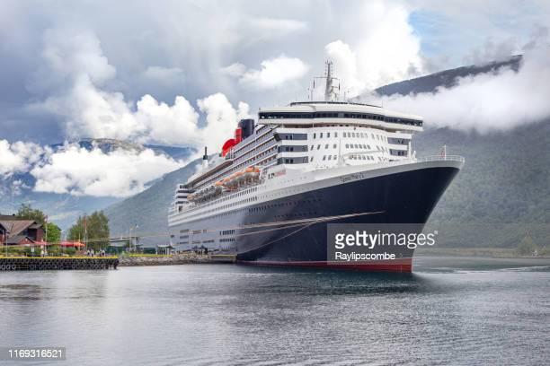 cunardのオーシャンライナーと旗艦、クイーンメアリー2は、周囲の山の風景の上に低くぶら下がっている雲に囲まれたノルウェーのフィヨルドのフラムの見事な会場にドッキングしました。 - rms クイーン メアリー 2 ストックフォトと画像