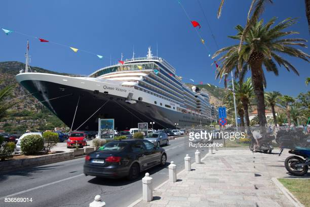 cunards, 'queen victoria' cruise ship moored at the tourist hotspot of kotor in montenegro, alongside a busy through road. - queen victoria stock pictures, royalty-free photos & images