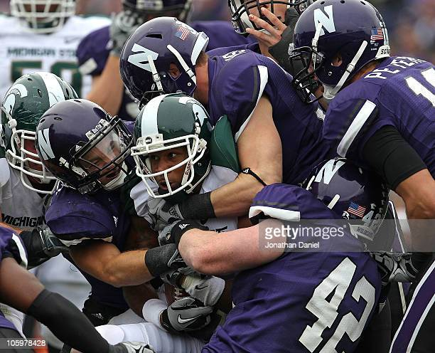 Cunningham of the Michigan State Spartans is stopped by Hunter Bates, Ben Johnson and Kevin Watt of the Northwestern Wildcats at Ryan Field on...