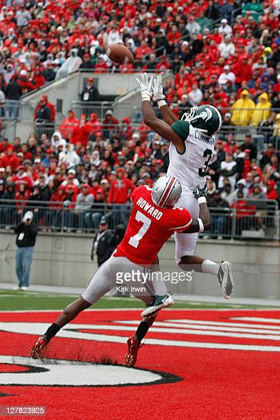 J Cunningham of the Michigan State Spartans jumps up and catches a pass for a touchdown while being covered by Travis Howard of the Ohio State...