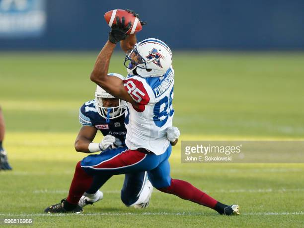 BJ Cunningham of the Montreal Alouettes makes a catch against Marcus Alford of the Toronto Argonauts during a CFL preseason game at BMO field on June...