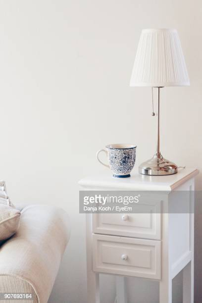 Cup And Lamp Shade On Side Table Against Wall At Home