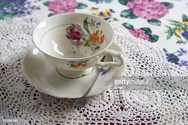 a cup and saucer on a table - doily ストックフォトと画像
