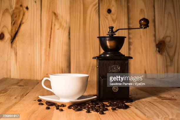 Cup By Grinder And Roasted Coffee Beans On Wooden Table