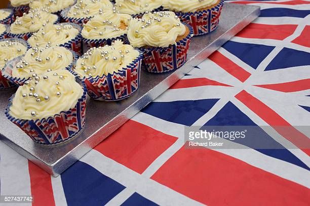 Cup cakes displayed on Union Jack table cloth at a neighbourhood street party in Dulwich south London celebrating the Diamond Jubilee of Queen...