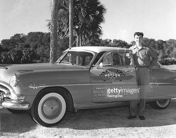 Cup champion Tim Flock poses with a street version of the Hudson Hornet he was awarded by the Hudson Motor Car Company for winning the title that year