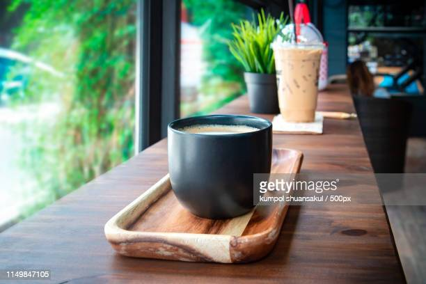 cup coffee with hand on the table in coffee shop - living room stockfoto's en -beelden