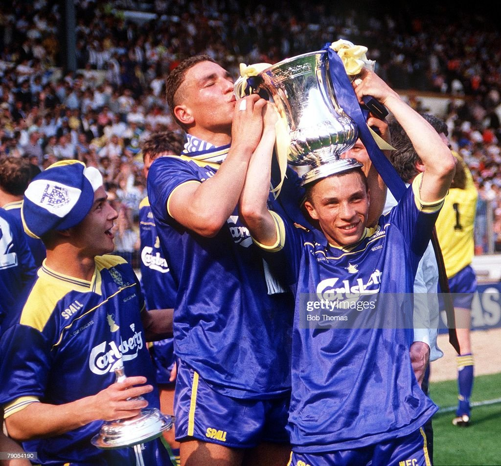 F.A.Cup Final. Wembley. 14th May 1988. Liverpool 0 v Wimbledon 1. Wimbledon's Vinnie Jones kisses the cup which is held by Terry Phelan, as Dennis Wise looks on. : News Photo
