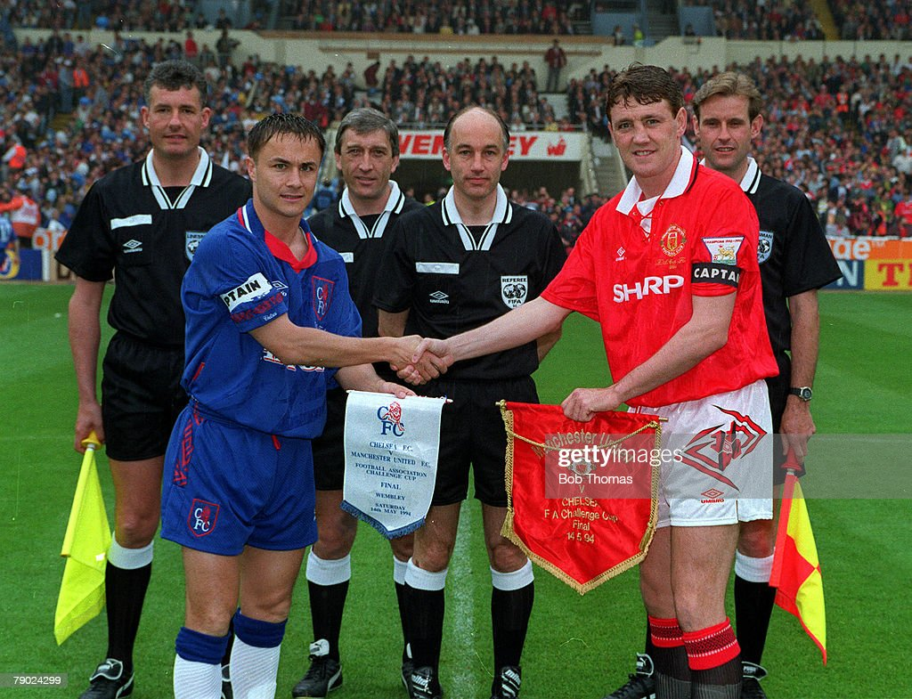 1994 FA Cup Final. Wembley. 14th May, 1994. Manchester United 4 v Chelsea 0. Manchester United's captain Steve Bruce shakes hands with Chelsea captain Dennis Wise (left) during the exchange of pennants before the match, watched by match officials, (refere : News Photo