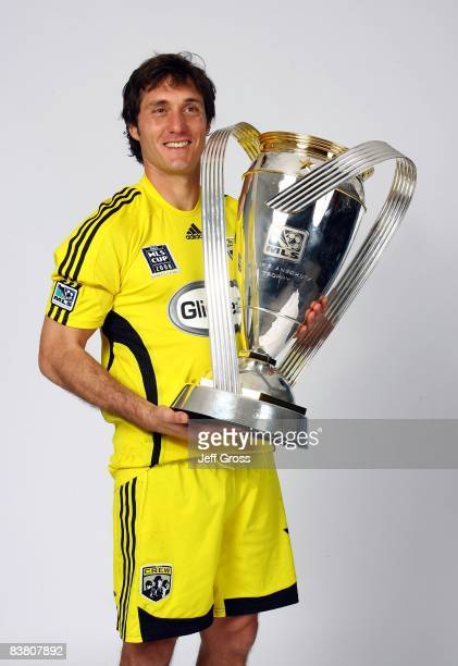 Cup MVP Guillermo Barros Schelotto of the Columbus Crew poses for a postgame celebration portrait with the Philip F Anschutz trophy after defeating...