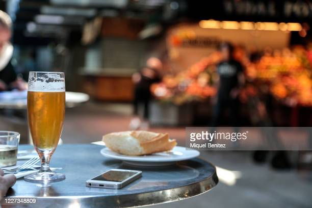 A cup of beer a smartphone and a piece of bread are seen at Pinotxo Bar in la Boqueria Market on May 27 2020 in Barcelona Spain All regions of Spain...