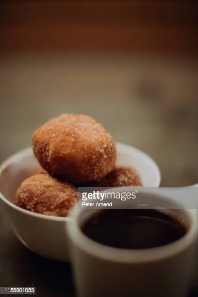 cup of black coffee and bowl of doughnuts on cafe table, close up shallow focus - imagenes gratis fotografías e imágenes de stock