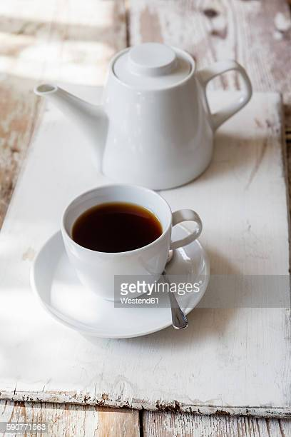 Cup of black coffee and coffee pot on wood