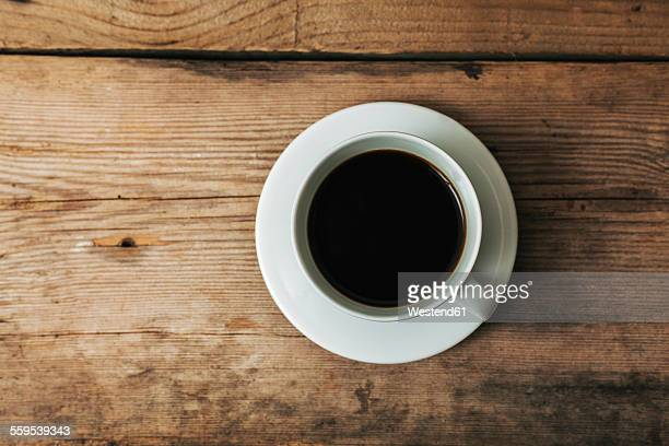 Cup of black coffee on wood