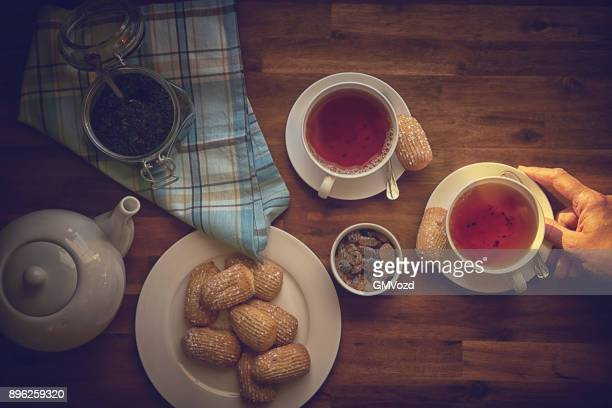 Tasse schwarzer Tee mit Gebäck serviert
