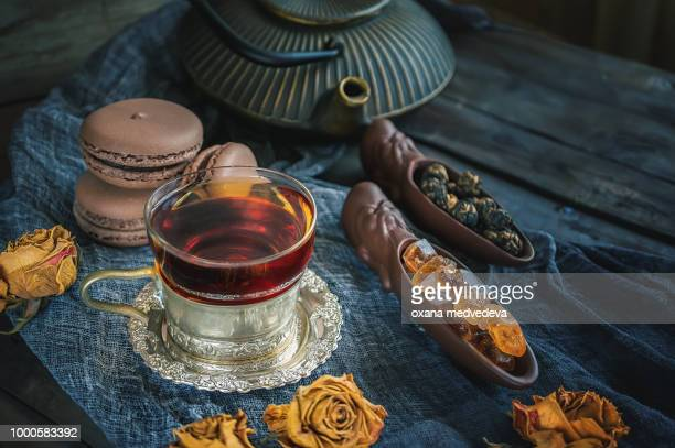 A Cup of brewed black tea. Two ceramic spatulas with caramel sugar and Rolled leaves in a large...