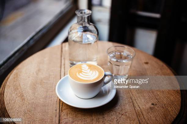 cup of cappuccino and still water on the table in a coffee shop, side view - coffee shop stock pictures, royalty-free photos & images