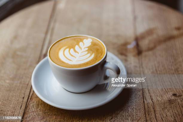 cup of cappuccino on a wooden table, close up - latte stock pictures, royalty-free photos & images