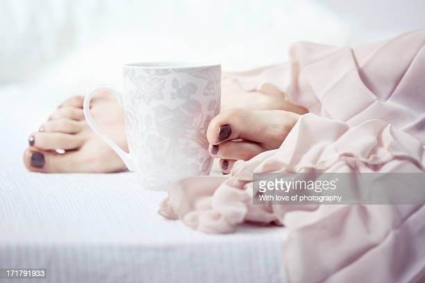 Cup of coffe and girl's feet in morning light