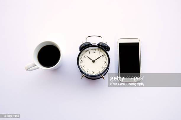 cup of coffee, alarm clock and smartphone on white background - countdown clock stock photos and pictures