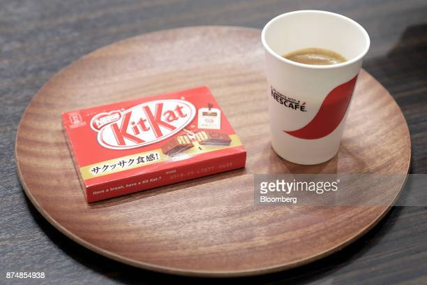 A cup of coffee and a box of KitKat chocolate bars sit on a tray during a media preview of the humanless cafe inside Nestle SA's Nescafe coffee shop...