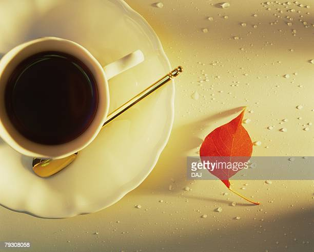 A cup of coffee and a colored leaf, Close Up, High Angle View