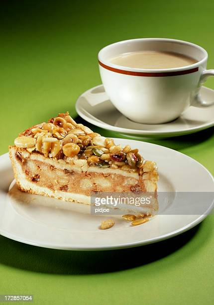 cup of coffee and apple pie topped with nuts