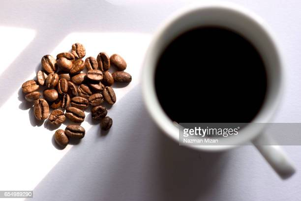 A cup of coffee and beans on white background. Focus on coffee beans.