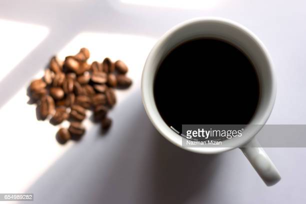 A cup of coffee and beans on white background. Focus on cup of coffee.