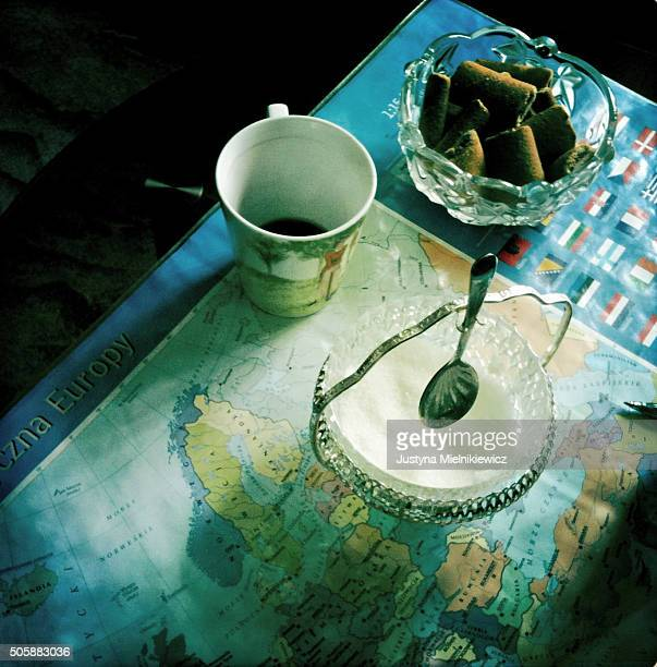 A cup of coffee and bowl of sugar stand on the table covered with a map of Europe in the office of International Marriage Agency Gimeney on July 20...