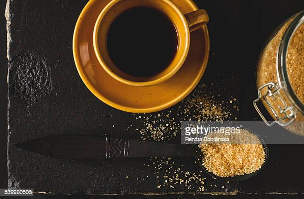 Cup of coffee and brown sugar on black tiles