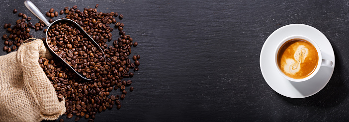 cup of coffee and coffee beans in a sack, top view 927414822