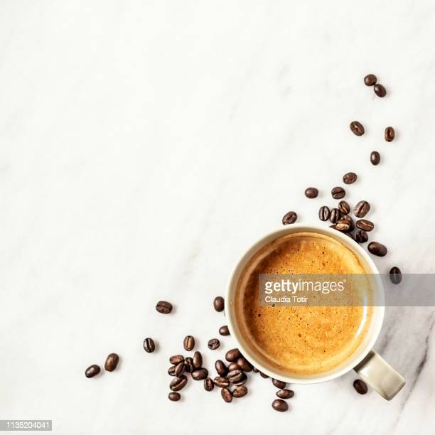 a cup of coffee and coffee beans on white, marble background - コーヒー ストックフォトと画像