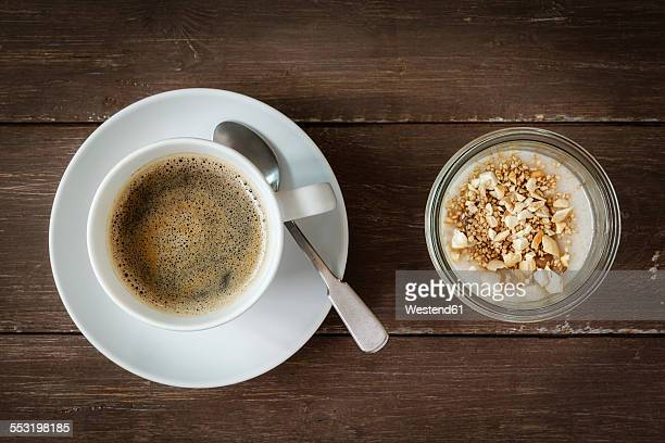 Cup of coffee and glass of vegan cocos pudding with banana and tapioca granules