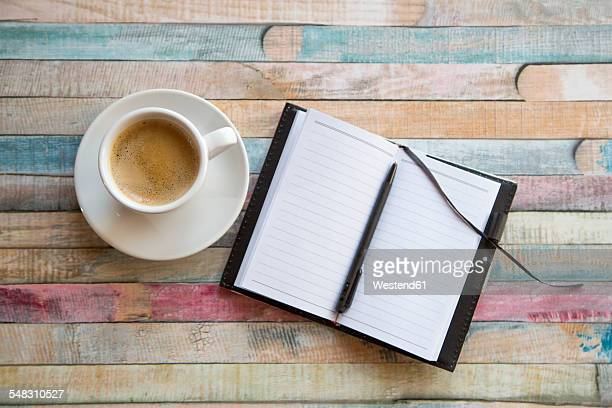 Cup of coffee and opened notebook