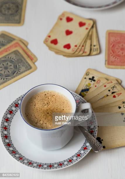 cup of coffee and playing cards on wooden table