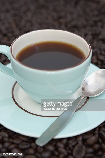 Cup of coffee and spoon on saucer