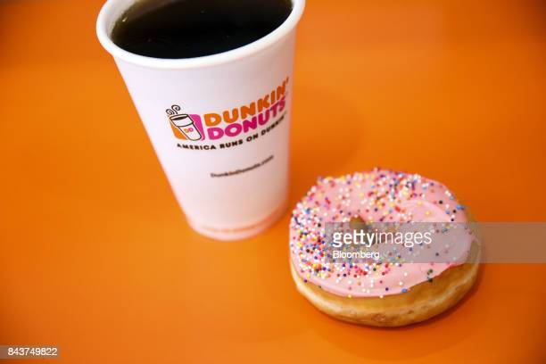 Cup of coffee and strawberry frosted donut with sprinkles are arranged for a photograph at a Dunkin' Donuts Inc. Location in Los Angeles, California,...