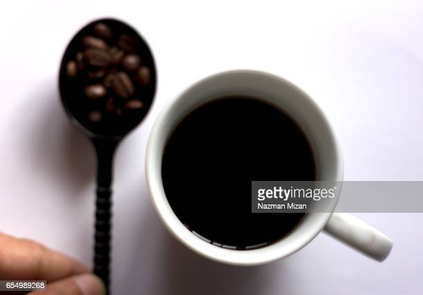 A cup of coffee and with beans in spoon on white background. A man holding the spoon.