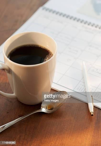 Cup of coffee beside calendar