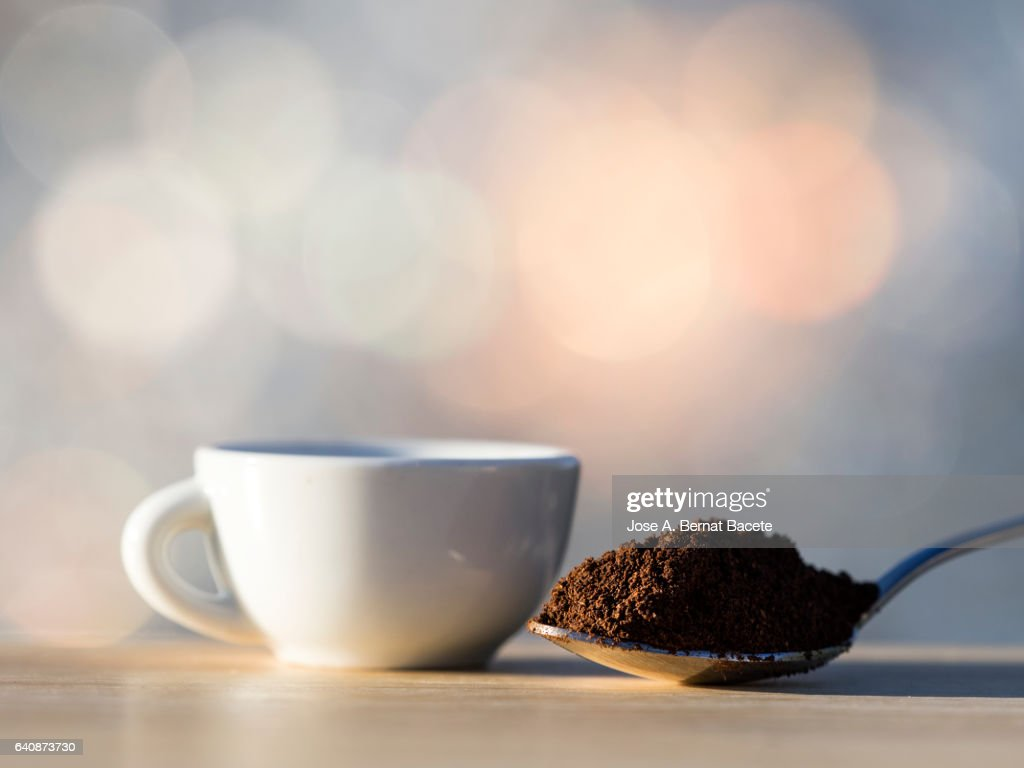 Cup of coffee espresso and teaspoon with a dosis of ground coffeeon a table of wood : Stock Photo