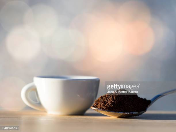 cup of coffee espresso and teaspoon with a dosis of ground coffeeon a table of wood - ground coffee stock photos and pictures