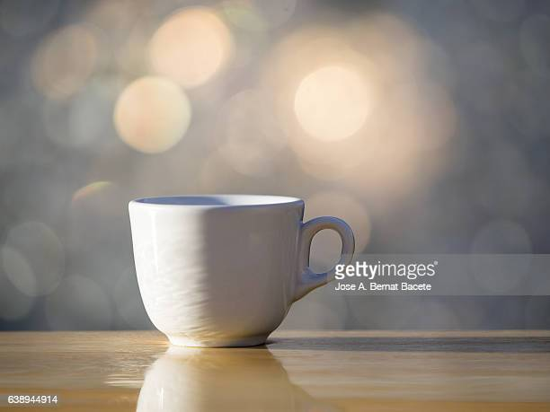 Cup of coffee espresso in a cup of white porcelain, on a table of wood illuminated by the light of the Sun