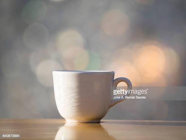 cup of coffee espresso in a cup of white porcelain, on a table of wood illuminated by the light of the sun - taza cafe fotografías e imágenes de stock