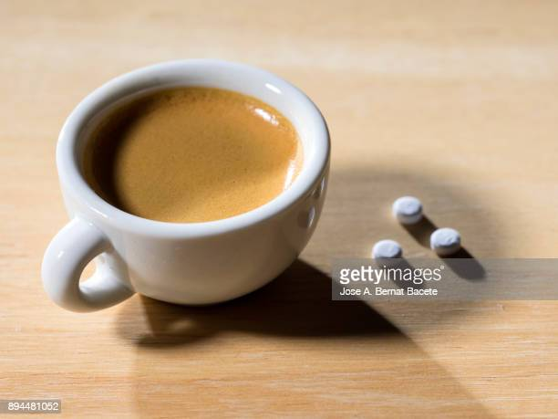 Cup of coffee espresso in a cup of white porcelain with a few tablets of saccharin, on a table of wood illuminated by the light of the sun outdoors. Spain.