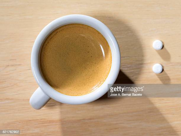 Cup of coffee espresso  with tablets of saccharin, on a table of wood