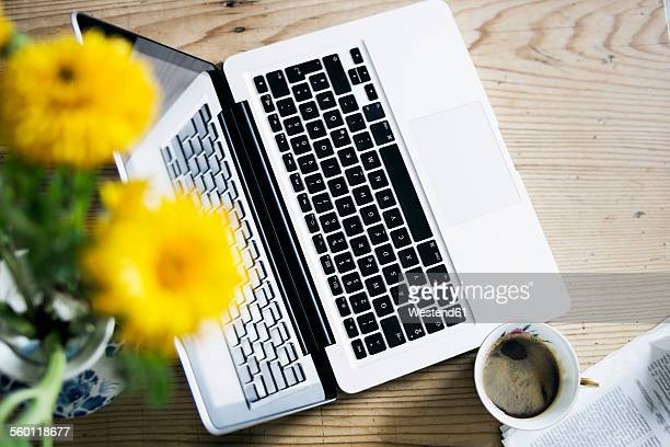 Cup of coffee, flowers, newspaper and laptop on wood